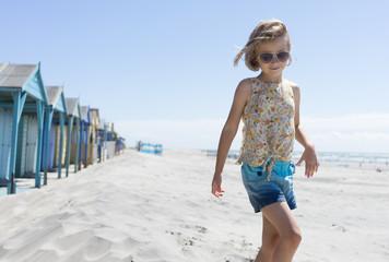 Girl walking on the beach next to beach huts