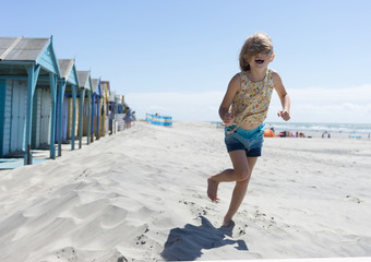 Girl running with hair over face on the beach and beach huts