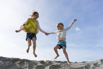 Two girls jumping off a sand hill