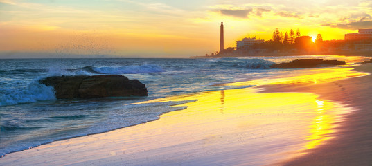 Beach and view of Maspalomas lighthouse at sunset.  Gran Canaria, Spain
