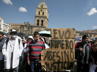 """Students from the UPEA hold a sign that reads """"Evo, Romero Killers, Justice"""" in a protest about a student dead last week during clashes with riot police, in La Paz"""
