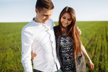 a young, happy, loving couple, standing in a green field, against the sky by the hands , and enjoy each other, advertising, and inserting text