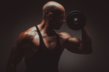 Strong young man bodybuilder performing exercise for biceps with heavy weights. Concept Gym Life Style.Toned Image.
