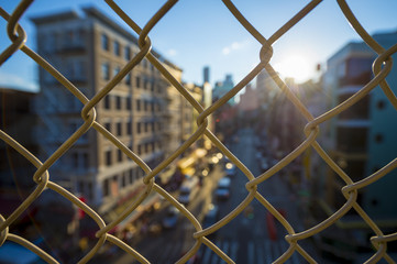 Downtown Manhattan and Chinatown viewed through a chainlink fence at sunset on the Manhattan Bridge.