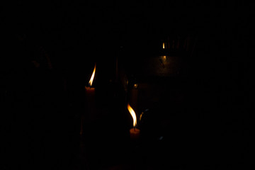 Orange fire of candles in darkness. Religious ritual of memory and pray. Human belief concept.