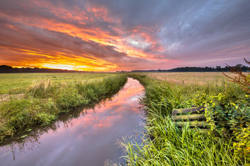 Warm indian summer sunrise over lowland river
