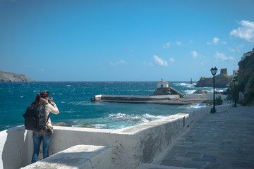 A young woman taking a photograph of a mediterranean church and lighthouse on the coastline of the Greek island of Andros