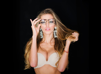 Woman attractive with big breasts wears old fashioned eyeglasses for vision. Girl short sightedness needs modern eyeglasses. Optics store concept. Sexy girl with makeup and earrings, dark background.