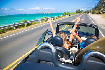 Road trip travel - girls driving car in freedom. Happy young girls cheering in convertible car on summer Hawaii vacations. Wall mural