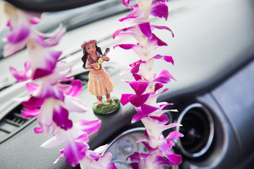 Hawaii road trip - car hula dancer doll dancing on the dashboard and Hawaiian Orchid Le Tourism and travel freedom concept.