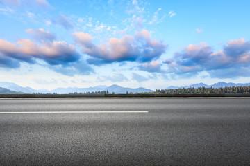 Asphalt road and hills with sky clouds landscape at sunset