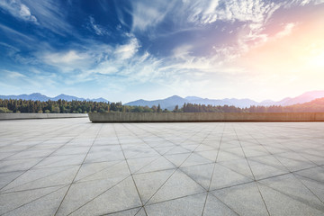 Empty square floor and hills landscape at sunset