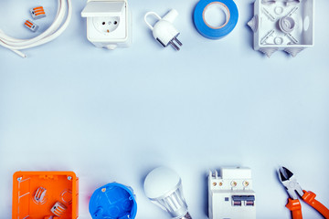 Electrical repair. Bulbs, socket outlet, cabel, screwdriver, pilers on grey background top view copy space