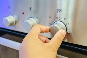Close up male hand while using the microwave in his kitchen