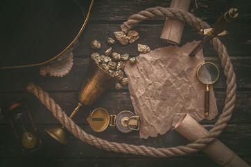 Pirate hat, goblet full of gold and treasure map crumpled parchment with copy space, dagger, compass and ship rope on old table background.
