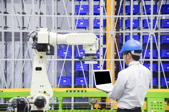 The programmer engineer control the robot for logistic warehouse.The hi-technology logistic industrial.