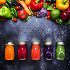Food and drinks, healthy and useful multicolored vegetable juices and smoothies with ingredients in glass bottles, set on gray background, top view