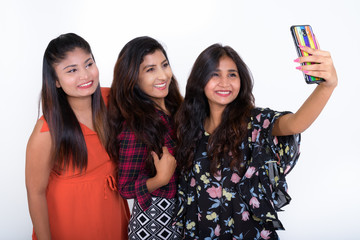 Three happy young Persian woman friends smiling while taking sel