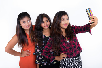 Studio shot of three happy young Persian woman friends smiling a