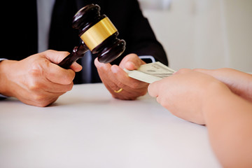 Lawyer businessman in suit hides money. A bribe in the form of dollar bills.