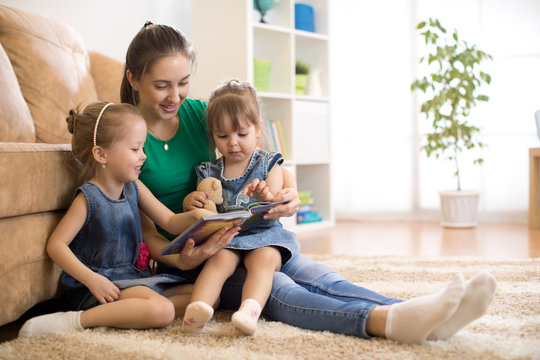 Happy mother and little kids daughters reading a book together in the living room at home. Family activity concept.