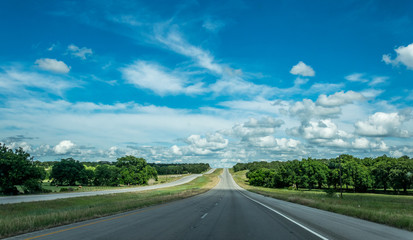 Rural road in Texas, USA. Agricultural landscape and blue sky