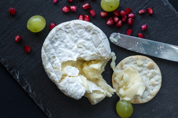 Camembert cheese on slate cheese board - top view photo