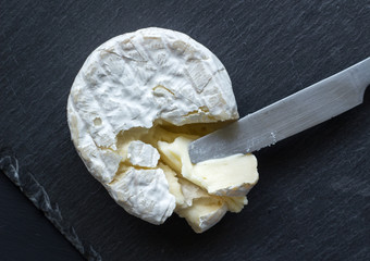 Camembert cheese on slate cheese board and knife - top view photo