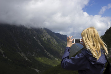 A lonely young blonde woman in a blue jacket stands in the mountains against the backdrop of a canyon and photographs a beautiful view. Concept. Tourism, traveling, hiking