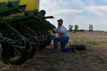 Cotton farmer Drew Malchoff works to replace a flat tire on his planting implement near Wakita, Oklahoma