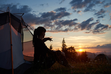 Attractive woman sits in a profile near a tent on the grass with wildflowers and shows her hand in the distance to the rising sun over the mountains. A fascinating landscape of the dawn in mountains