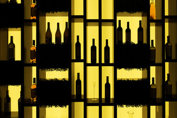 Wine bottles on a shelf illuminated from behind