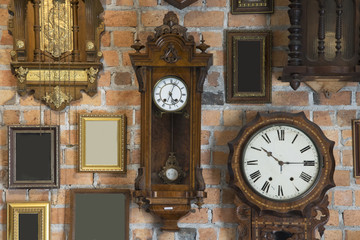 Collection of vintage clock and picture frame hanging on an brick wall