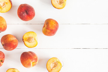 Peaches on white wooden background. Flat lay, top view, copy space