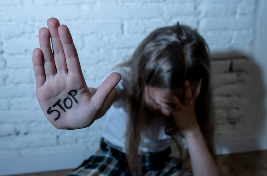 Pretty young girl showing the word stop written on her hand. Violence,abuse and bullying concept