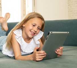 Happy cute kid learning, playing and surfing on the Internet with tablet with great interest