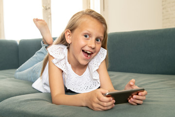 Portrait of a beautiful child lying on the sofa at home smiling and playing with mobile phone
