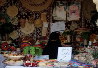 A Saudi woman sits in her shop at heritage village during Gulf Coastal Cultural Festival at Dammam Corniche, Dammam