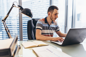 Businessman working on laptop using internet searching for information sitting at desk in office