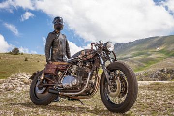 Biker with black leather suit and mask stay rear of his custom special rat motorbike.  Desolated mountain landscape in the background. Post apocalyptic concept