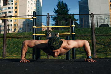 A young man doing squeezing at the stadium, an athlete, outdoor training in the city copy space