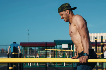 Young man doing exercises on the uneven bars in the stadium, athlete, outdoor training in the city copy space