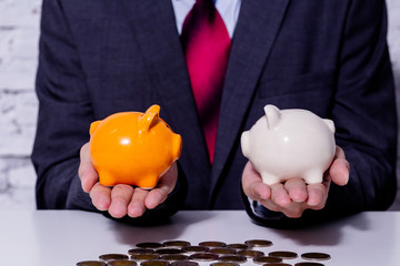 Businessman making a comparison and difference between each money piggy bank - finance issue comparison concept.