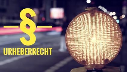 Baustellenlampe und Verkehr bei Nacht mit der Aufschrift § Urheberrecht zur Verdeutlichung von Urheberrechtsverstößen
