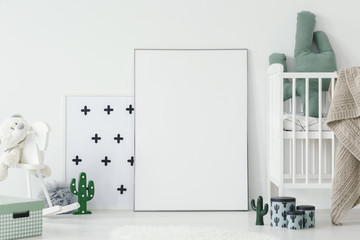 Cactus pillow in white cradle next to empty poster with mockup in baby's room interior. Real photo