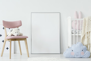 Plush toy on pink chair and blue pillow in child's room interior with mockup of poster. Real photo