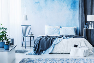 Blue chair next to bed with grey blanket in cozy bedroom interior with plants on white cupboard