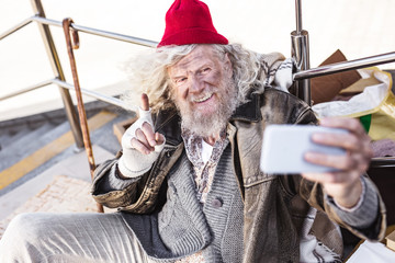 Photo to remember. Delighted bearded man looking into the smartphone camera while taking a selfie