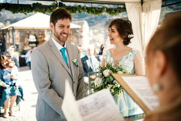 Charming newlyweds smile standing before a wedding altar