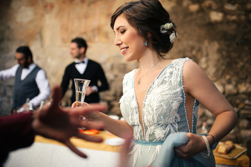 Bride in blue dress drinks champagne standing with guests